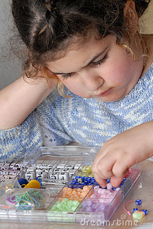 Little Girl Plays with Beads