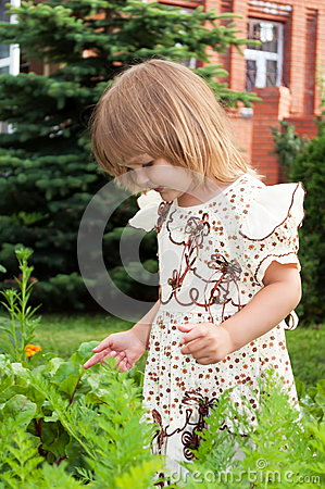 Little girl plays in garden