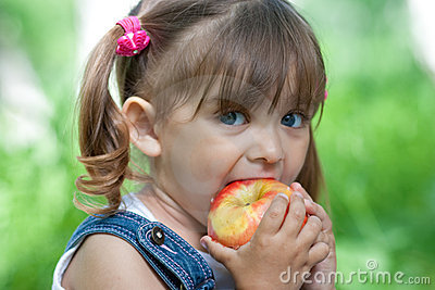 Little girl portrait eating apple outdoor