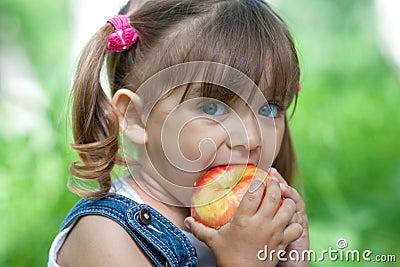 Little girl portrait eating apple outdoor