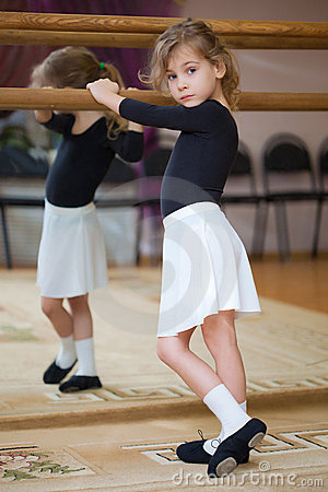 Little girl poses at ballet barre