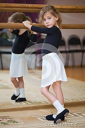 Little girl poses at ballet barre