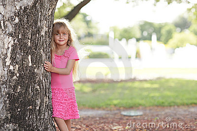 Little girl posing behind the tree