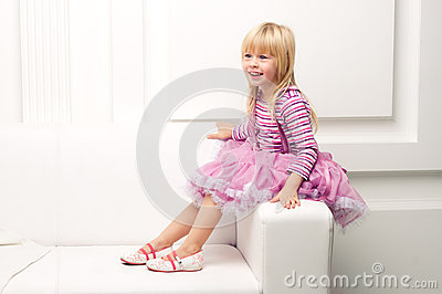 Little girl posing happily on sofa