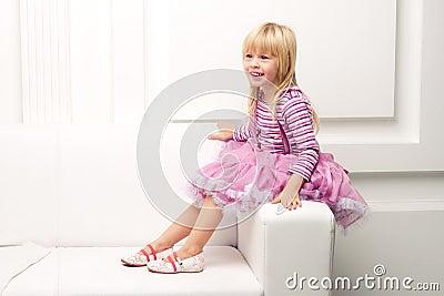 Little girl posing happily on sofa