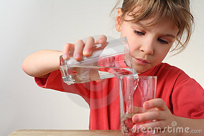 Little girl pour out water from one glass to other