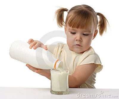 Little girl pouring milk in glass