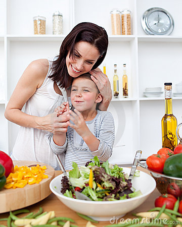 Little girl preparing a salad with her mother
