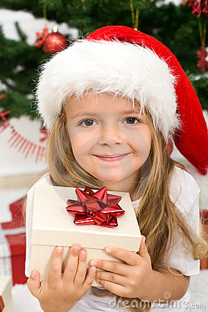 Little girl with present and christmas hat