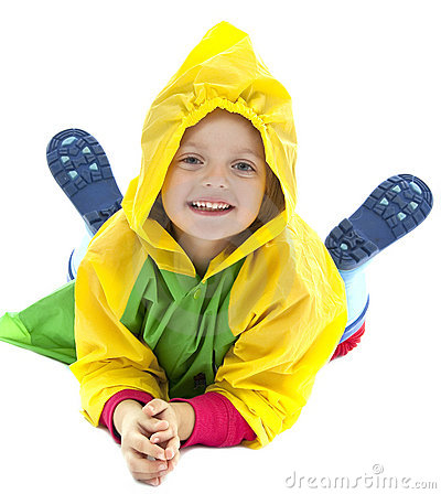 Little girl with raincoat playing on the ground