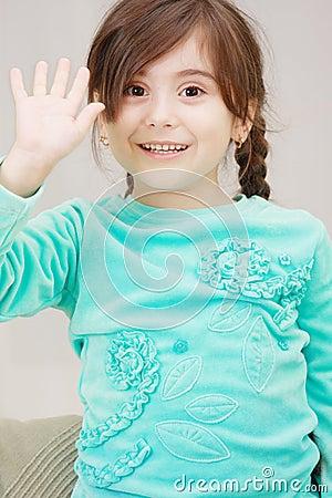 Little girl raises hand in greeting