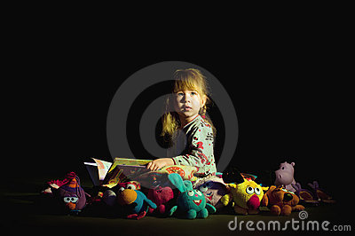 Little girl reading book before goes to sleep