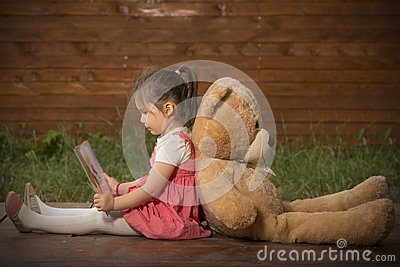 little girl reading a book to her teddy bear stock photo