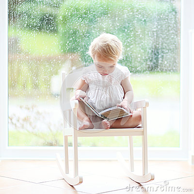 Little girl reading in front of big window for Chair next to window