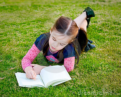 A little girl reading on the grass - from above