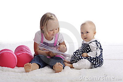 Little girl reading a story for her sister