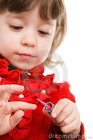 Little girl in red applying polish on nails