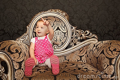 Little girl in red dress sitting on retro armchair