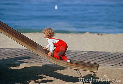 Little girl in red overralls climbing up slide Editorial Stock Image