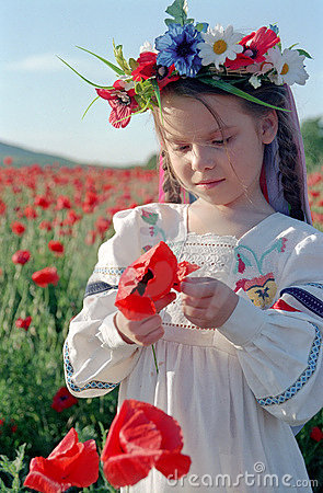 Little girl on red poppy field