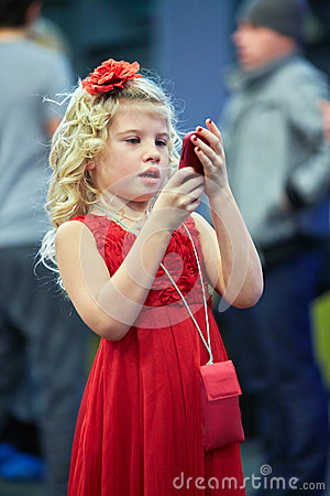 Little girl  with red rose in hair looks at cell phone