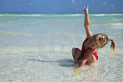 Little girl in red swimsuit playing   in the sea