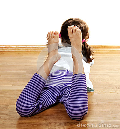A little girl resting on a wooden floor