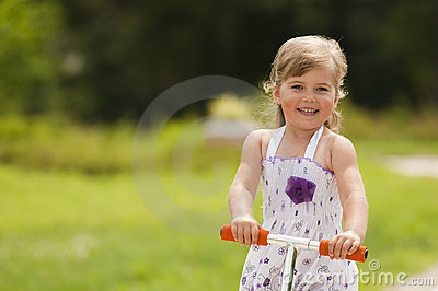 Little girl ride the scooter in the park