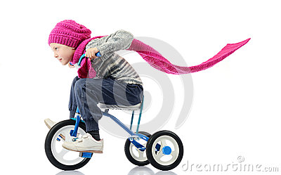Little girl rides a bicycle on white