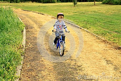 a little girl rides a bike in the park