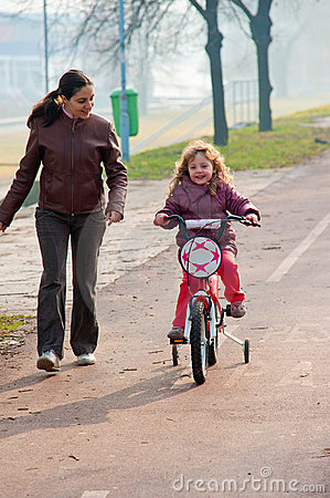 Little girl riding a bike, bycicle with mother