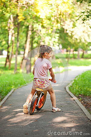 Little girl riding a bike on a sunny day