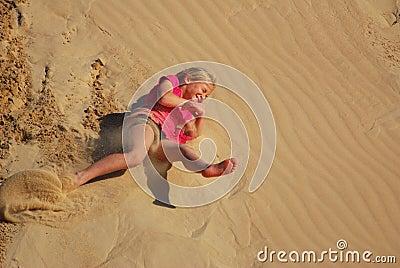 Little girl rolling down sand dune