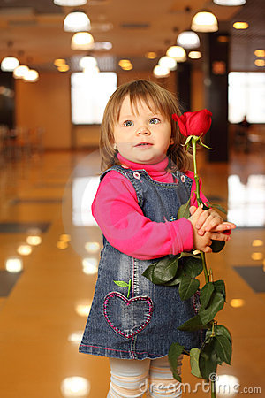 Little girl with rose in hands stand in cafe