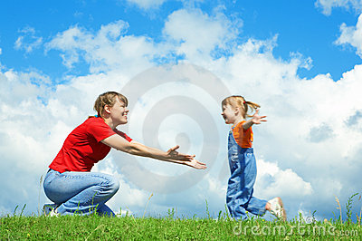 Little girl run to mother embrace on green grass