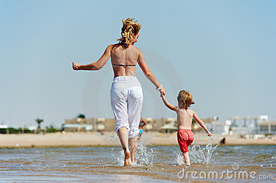 Little girl running on sandy red sea shore