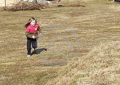 Little girl running with a sling-shot