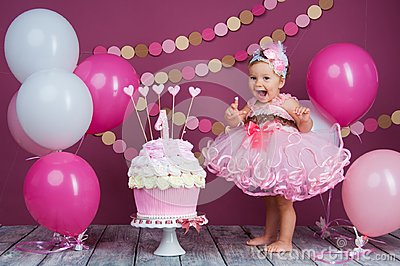 The little girl`s birthday girl was smeared into a cake. The first cake. The use of the first cake. Smash cake. Stock Photo