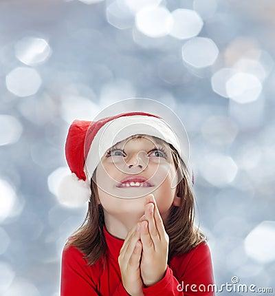 A little girl with a santa cap snowy bokeh