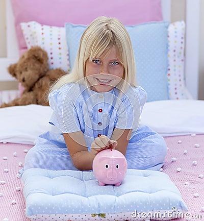 Little girl saving money in a piggy bank