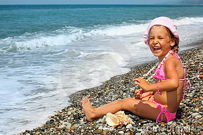Little girl with seashell and necklace on seacoast
