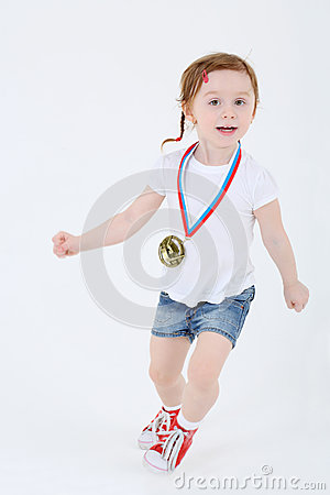 Little girl in shorts with medal on her chest runs