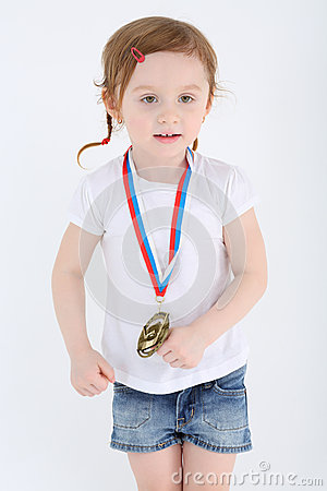 Little girl in shorts with medal on her chest stands and looks