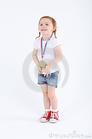 Little girl in shorts with medal on her chest stands and smiles