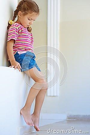 Little girl in shorts sitting