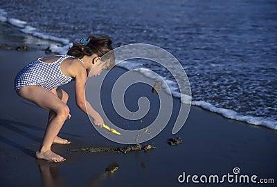 Little girl shoveling sand on