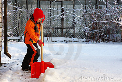 Little girl shoveling snow with shovel