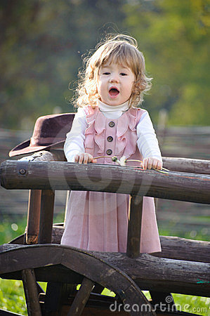 Little girl singing near wooden fence