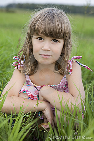 Little girl sitiing in meadow