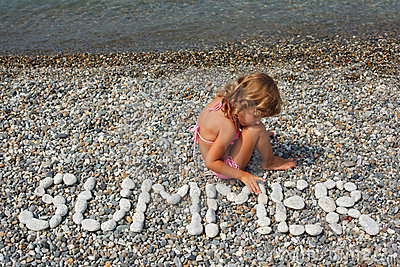 Little girl sits on beach near to water.